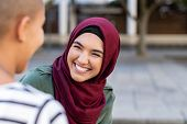 Portrait of cheerful woman in hijab smiling while talking to bald friend. Best friends on street lau poster
