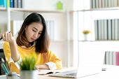 Young Attractive Asian Woman Or Student Working On Thesis Assignment Or Studying Online In Self E-le poster