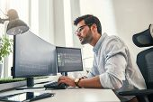 Confident Businessman. Young Bearded Trader In Formal Wear Is Analyzing Trading Charts On Computer S poster