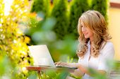 woman with laptop in the garden. internet outdoors own