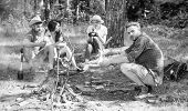 Hikers Sit Near Campfire Relaxing While Wait Roasting Food. Hikers Organized Quick Picnic To Eat And poster