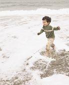 Boy splashing through ocean surf