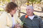 stock photo of oxygen  - Senior Woman Outside with Seated Man Wearing Oxygen Tubes - JPG