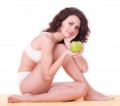 Beautiful young woman with green apple on white background.
