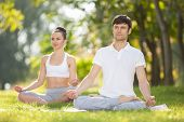 Couples Yoga outdoor. Man and woman doing yoga exercises, meditate in the park. Concept of healthy l poster