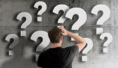 Rear View Of Puzzled Man Scratching His Head Against Concrete Wall Filled With Question Marks poster