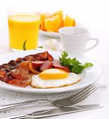 Breakfast with bacon, fried egg and orange juice on white isolated background