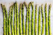 Asparagus spears on parchment paper over oven tray, ready for roasting.  With olive oil and pepper. poster