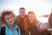 Group Of Friends Resting On Mountain While Hiking. Hikers Relaxing And Taking Selfie. Friends Taking poster
