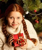 redhair woman with Christmas Gift in a house interior