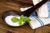 Old spoon with natural sweetener stevia and a fresh stevia leaf