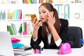 young business woman looking in the mirror and putting some makeup by office work