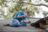stock photo of rotten  - Man using crowbar to remove rotten wood from leaky roof - JPG