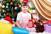 Little girl sits near a Christmas tree with gift in hand in festively decorated room
