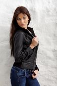 foto of straight jacket  - Glamorous young woman in black leather jacket posing near white wall - JPG