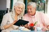 stock photo of hot couple  - Senior Couple Using Tablet Computer At Outdoor Cafe - JPG