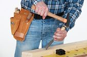 foto of chisel  - Tradesman chiseling a plank of wood - JPG