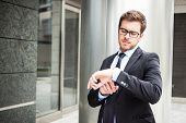 picture of late 20s  - Handsome businessman checking time on his watch - JPG