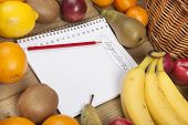 Book and pencil amidst fruits
