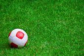 A red and white soccer ball on grass. Uma bola de futebol branca e vermelha na grama.