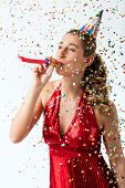 Woman celebrating birthday and hooting with horn at a shower of confetti
