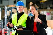 Teamwork - female supervisor and warehouseman or forklift driver with laptop and cell phone at wareh