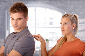 Angry girlfriend poking shoulder of boyfriend with finger looking upset.