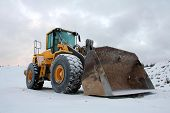 picture of wheel loader  - Yellow wheel loader at sand pit in winter snow - JPG