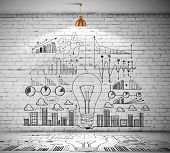 Drawn business plan on wall illuminated by lamp above