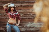 stock photo of cowgirl  - beautiful cowgirl style model posing on farmland near wood wall - JPG