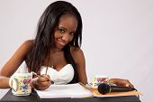 Black woman studying and smiling at the camera