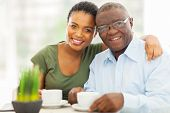 image of grandfather  - beautiful young adult african girl and father having coffee at home - JPG
