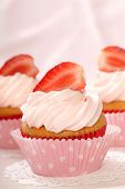Delicious vanilla cupcake with strawberry frosting and fresh strawberries