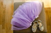 foto of settee  - girls blown lilac ballerina skirt and light gray shiny shoes lying on the settee - JPG