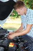 Young driver uses multimeter voltmeter to check voltage level in car battery