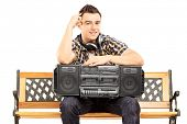 Smiling guy holding a boombox seated on a wooden bench isolated on white background