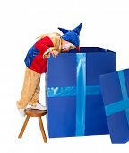 Funny jester clown girl looking deep into a big blue surprise box