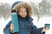 image of thermos  - Funny small boy invites to drink hot tea from thermos at winter park - JPG