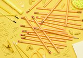 School supplies. Pencils, erasers, paper clips, brushes, pins, scissors, paper laying in a random pattern on a yellow background. Everything in a shade of yellow..