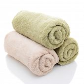 Three rolled bath towels freshly laundered on a white background with reflection. Closeup looking at