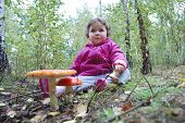 stock photo of face-fungus  - Little girl sitting in a forest near the fly agaric - JPG