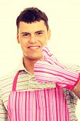 Man against a white background, wearing a pink kitchen apron.