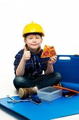 Little funny mechanic boy eating pizza among tools