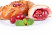 Fresh baked pasties with cherry on plate close-up
