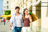 Young couple shopping in inner city ith shopping bags spending money