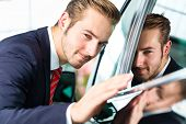 Seller or car salesman in car dealership presenting the reflecting car paint of his new and used car