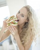 Portrait of impatient woman eating large sandwich in house