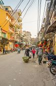 HANOI, VIETNAM, JANUARY 13, 2013 - busy street in Old Quarter, with small stores, street sellers and