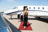 Rear view of rich woman walking towards private jet while pilot and stewardess standing at airport t