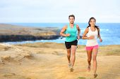 Sports couple jogging for fitness running in beautiful landscape nature outdoors. Young female and m